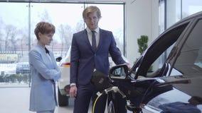 O vendedor profissional seguro diz a uma menina bonita em um terno à moda os detalhes e as características de um elétrico novo filme