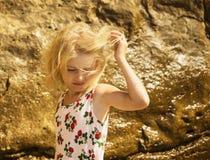 O vento está jogando o cabelo na menina loura na praia imagens de stock royalty free
