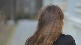 O vento funde o cabelo escuro longo da menina glamoroso elegante que veste o revestimento elegante preto que levanta na câmera St video estoque