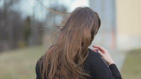 O vento funde o cabelo escuro longo da moça bonita que anda longe da câmera, olha para trás, revestimento do outono Steadicam, le video estoque