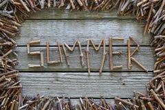 O verão da inscrição com as varas de madeira no fundo de madeira Fotografia de Stock Royalty Free