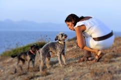 O verão da mulher e dos cães encalha a cena no mar que joga junto Imagens de Stock Royalty Free