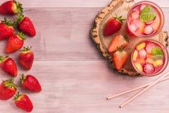 O verão de refrescamento bebe com morango, limão e gelo Imagem de Stock Royalty Free