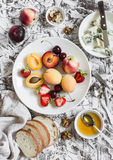 O verão frutifica - abricós, pêssegos, ameixas, cerejas, morangos e queijo azul, mel, nozes, pão em um backgroun de pedra claro Imagem de Stock