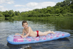 O verão no menino do rio senta-se em um colchão inflável no ri Fotografia de Stock