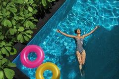 O verão relaxa Mulher que flutua, água da piscina Feriado do verão Imagem de Stock Royalty Free