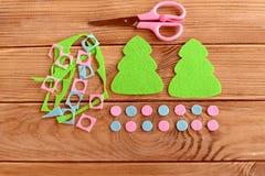 O verde dois sentiu as bolas ajustadas, tesouras das árvores de Natal, as cor-de-rosa e as azuis, sucatas de feltro em uma tabela Imagem de Stock Royalty Free