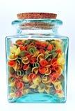 O verde, vidro, considera completamente o frasco com a tampa da cortiça que contem escudos coloridos da massa. imagens de stock royalty free