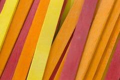 O vermelho, amarelo e a laranja coloriram o fundo das varas do picolé Fotos de Stock Royalty Free