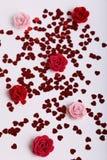 O vermelho bonito dispersou corações da lantejoula com flores da tela em um fundo branco Fotografia de Stock Royalty Free
