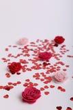 O vermelho bonito dispersou corações da lantejoula com flores da tela em um fundo branco Imagem de Stock
