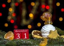 O vermelho cuba calendário data o 31 de dezembro, a placa dos doces com marshmallow e o caramelo como o fundo do cão de luzes ama Imagem de Stock
