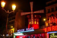 O vermelho de Moulin é a taberna mundialmente famosa em Paris em Montmartre Uma luz muito eficaz da noite e umas lâminas de geren imagens de stock