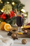 O vermelho do Natal ferventou com especiarias o vinho no vidro na placa de madeira no fundo branco imagens de stock royalty free