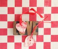 O vermelho e o branco verificam com os corações e a palavra do amor Foto de Stock Royalty Free