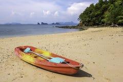 O vermelho e Yellow Sea canoe na praia só fotos de stock royalty free