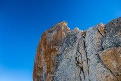 O vermelho matizou a rocha corroída do granito contra o céu azul Fotos de Stock