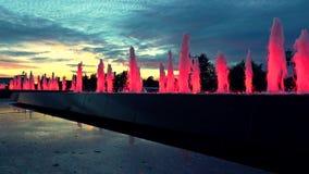 O vermelho moderno iluminou fontes do parque no por do sol atrasado Iluminação arquitetónica do diodo emissor de luz Imagem de Stock