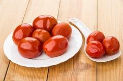 O vermelho pôs de conserva tomates na placa branca, colher plástica na tabela Fotografia de Stock Royalty Free