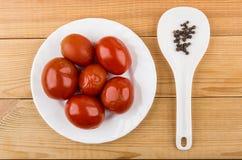O vermelho pôs de conserva tomates na placa branca e na pimenta preta Imagem de Stock Royalty Free
