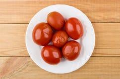 O vermelho pôs de conserva tomates na placa branca na tabela de madeira Imagens de Stock