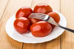 O vermelho pôs de conserva tomates na placa e na forquilha na tabela Imagens de Stock Royalty Free