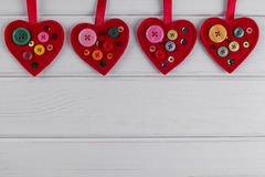 O vermelho sentiu os ofícios dos corações decorados com grânulos e botões no fundo branco imagens de stock