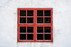 O vermelho velho resistiu à janela com quadrados na parede branca com textura gasta Fotos de Stock Royalty Free