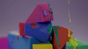 O verniz para as unhas colorido flui abaixo da superfície da esponja da composição filme