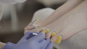 O verniz transparente de aplicação mestre do pedicure aos pregos do dedo do pé do cliente no salão de beleza filme