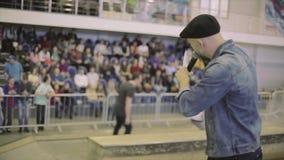 O verso do homem no chapéu fala no microfone com os povos no skatepark audiências competição anfitrião video estoque