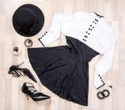 O vestido bonito com botões e acessórios arranjou no assoalho Imagens de Stock Royalty Free
