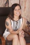 O vestido branco da mulher senta o sorriso da tatuagem da garra imagem de stock royalty free
