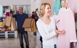 O vestido da compra da esposa na loja de fato, homem é furado foto de stock