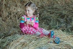 O vestido da menina trançada pequena e as botas de goma vestindo que sentam-se no país cultivam o hayloft no feno fraco secado da Foto de Stock