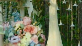 O vestido de casamento branco longo pendura no pinheiro em um esclarecimento nas madeiras video estoque