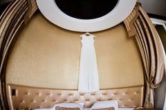 O vestido de casamento branco pendura em um interior bonito Fotografia de Stock Royalty Free