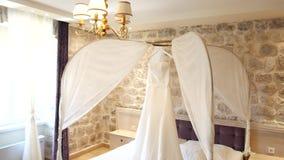 O vestido de casamento da noiva pendura sobre a cama Coleções o vídeos de arquivo