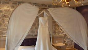 O vestido de casamento da noiva pendura sobre a cama Coleções o video estoque