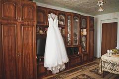 O vestido de casamento das noivas que pendura em um gancho na sala 9365 imagem de stock