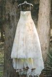 O vestido de casamento do vintage pendura de uma árvore imagens de stock royalty free