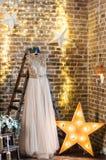 O vestido de casamento dourado está pendurando em uma escada em um fundo do sótão imagens de stock