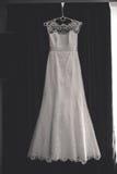 O vestido de casamento lindo pendura na cortina Fotografia de Stock Royalty Free