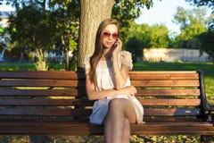 O vestido de riso do rosa dos vidros do verão do parque do telefone da menina moreno emocional bonita, aprecia seu feriado na cid fotos de stock