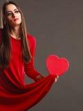 O vestido vermelho da mulher guarda a caixa dada forma coração Imagens de Stock