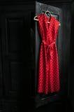 O vestido vermelho em um branco pontilha em um gancho de madeira Fotografia de Stock Royalty Free