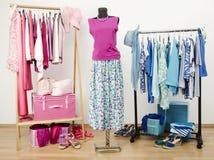 O vestuário com com roupa cor-de-rosa e azul arranjou em ganchos Equipamento bonito do verão em um manequim Imagem de Stock