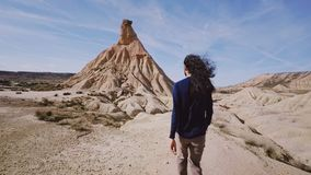 O viajante alto anda através do deserto no dia ensolarado quente filme