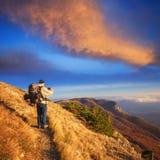 O viajante com uma trouxa está no trajeto rochoso na montagem outonal Foto de Stock