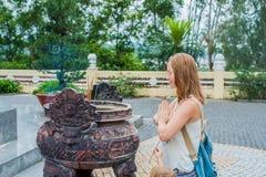O viajante da jovem mulher que reza na ação polida com incenso cola no templo do buddhism em Vietname Foto de Stock